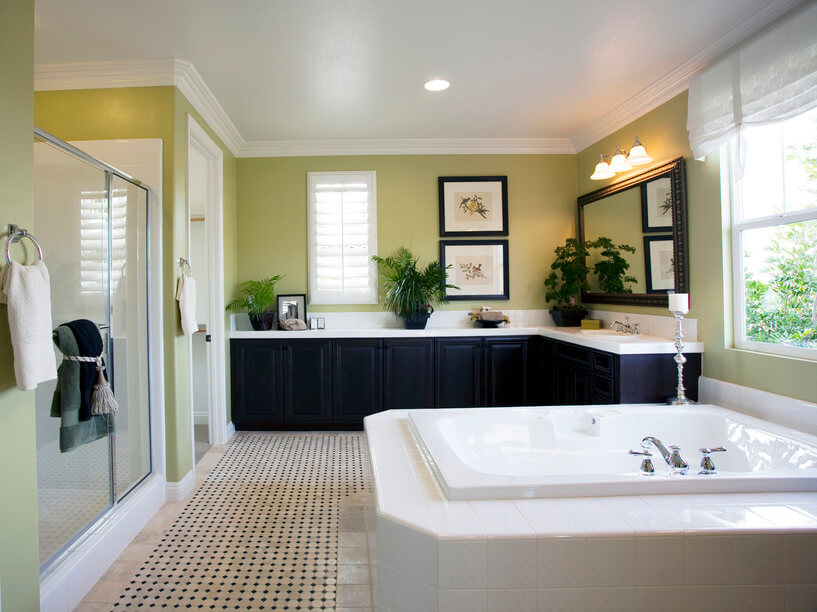 Neat and tidy bathroom with walls painted in light brown and light green, touched up with a white sink, brown/black tiling and patterns, contrasted with black wood vanities.