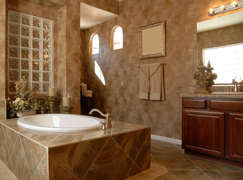 A rustic inspired bathroom. Dark brown wood vanity, light brown patterned sink and floor tilings and tan wall painting.
