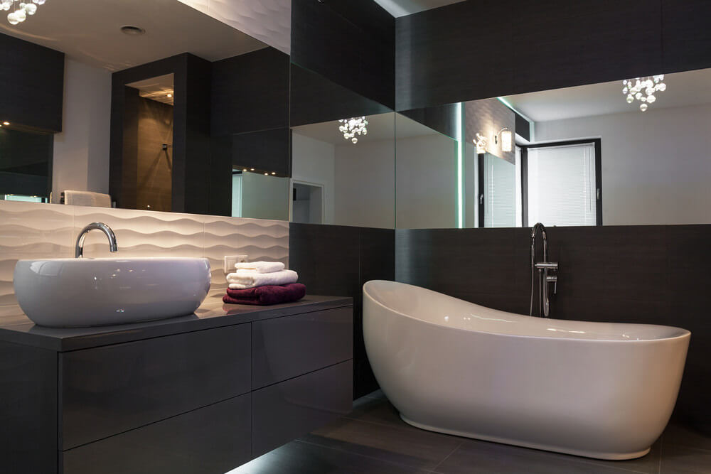 Black wood vanity and walls are highlighted with white sink and bath tub and accented by a dark brown floor.