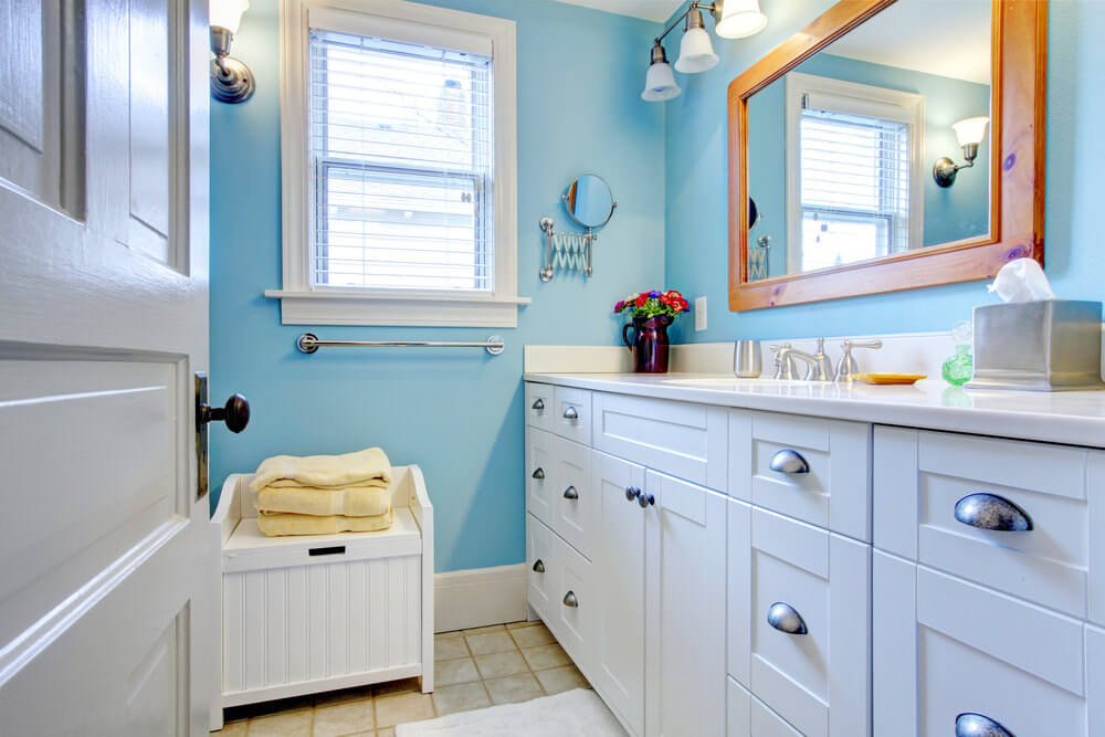 The echo blue wall paint and white vanities resemble nicely weathered blue skies, touched with light yellow floor tiles and wood wall mirror.