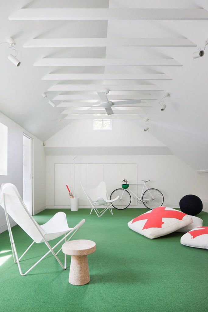 Upstairs, we see this recreation room flush with bold green carpeting. The vaulted ceiling is crossed with white exposed beams, hanging far above a sparse set of furniture that allows for plenty of activity room.