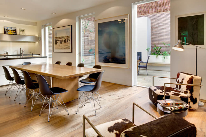 The kitchen area is more subdued, with a large natural wood table at center and cowhide armchairs to the side. Between large glass openings to the patio, we see more art pieces.