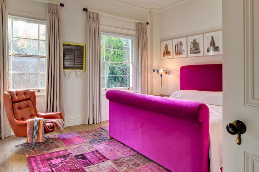 The art studio was transformed into this bold primary bedroom, with bright purple bed frame, throwback style leather armchair, and even more art prints surrounding.