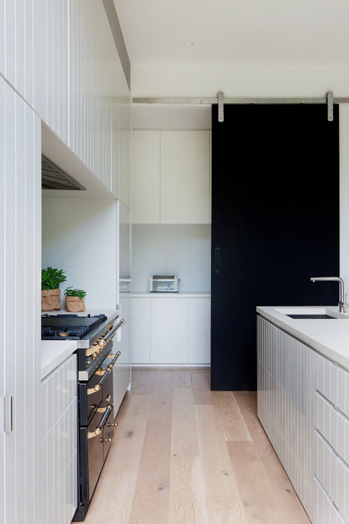 In the kitchen, we see sleek white countertops and a black oven with gold hardware, completing a very high contrast look. The sliding panel door in the background adds to the contrast as well.
