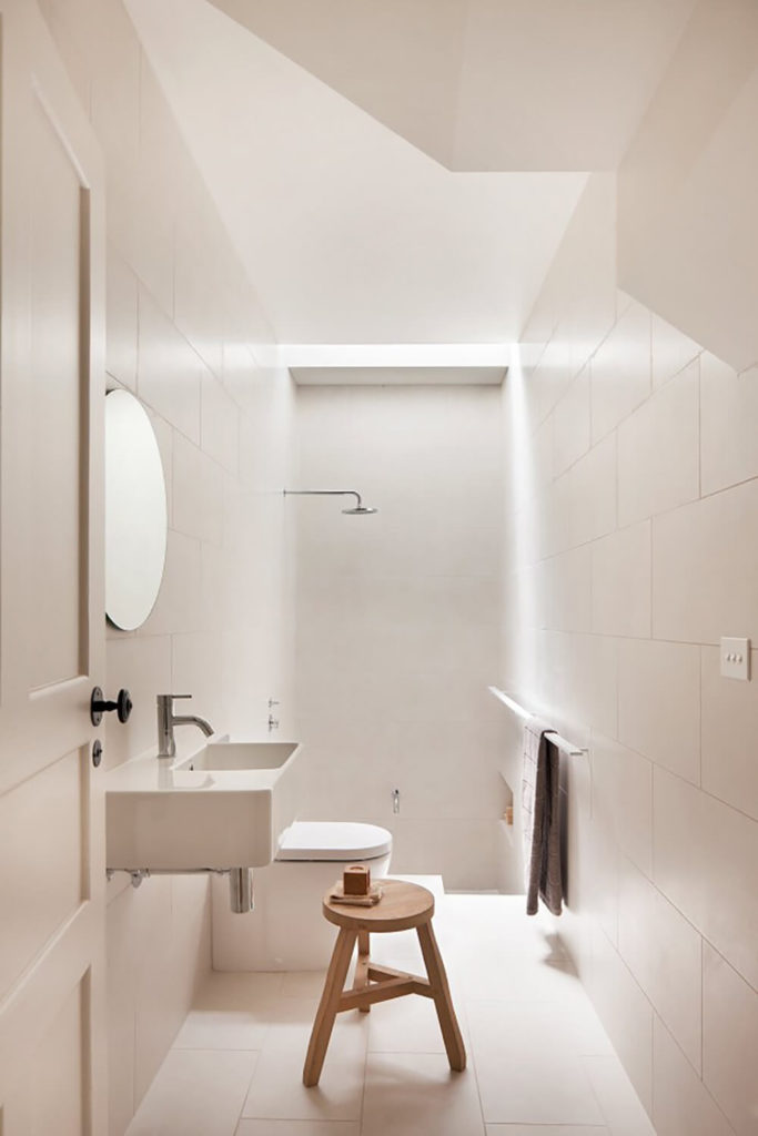 The bathroom is awash in white large format tile, from the flooring on up. A simple floating vanity hangs near the walk-in shower, with no dividing enclosure between.