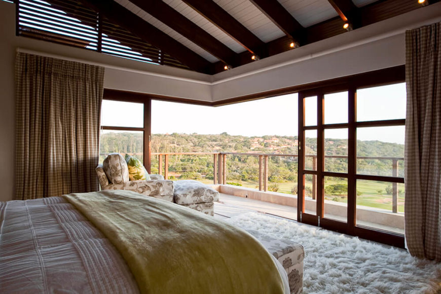 The upper level houses the primary bedroom, which boasts a similarly broad opening to the outdoors. Sliding glass panels surround the room entirely, allowing for a total blurring of the line between indoors and out.