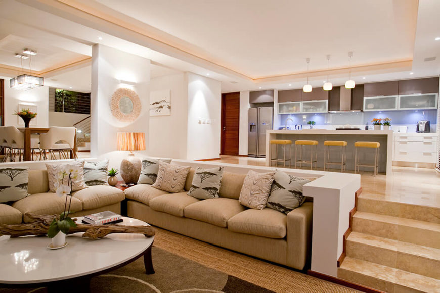 The open plan layout blends the living room with the large kitchen, at right. A lowered floor and small surrounding wall help define it within the larger space.