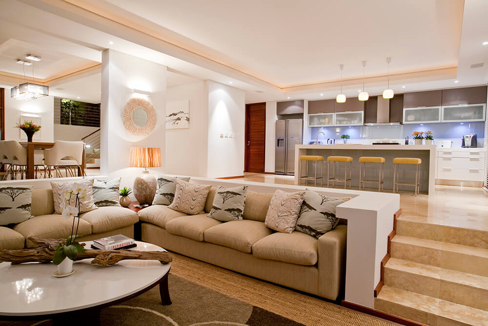 Large and stylish great room with a large sofa set and a cozy kitchen setup both under the classy tray ceiling featuring recessed and pendant lights.