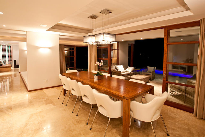 The dining area, within the same large open room, features a rich natural wood table and sleek white chairs, contrasting with the marble flooring. Here, we see another large sliding glass opening to the patio.