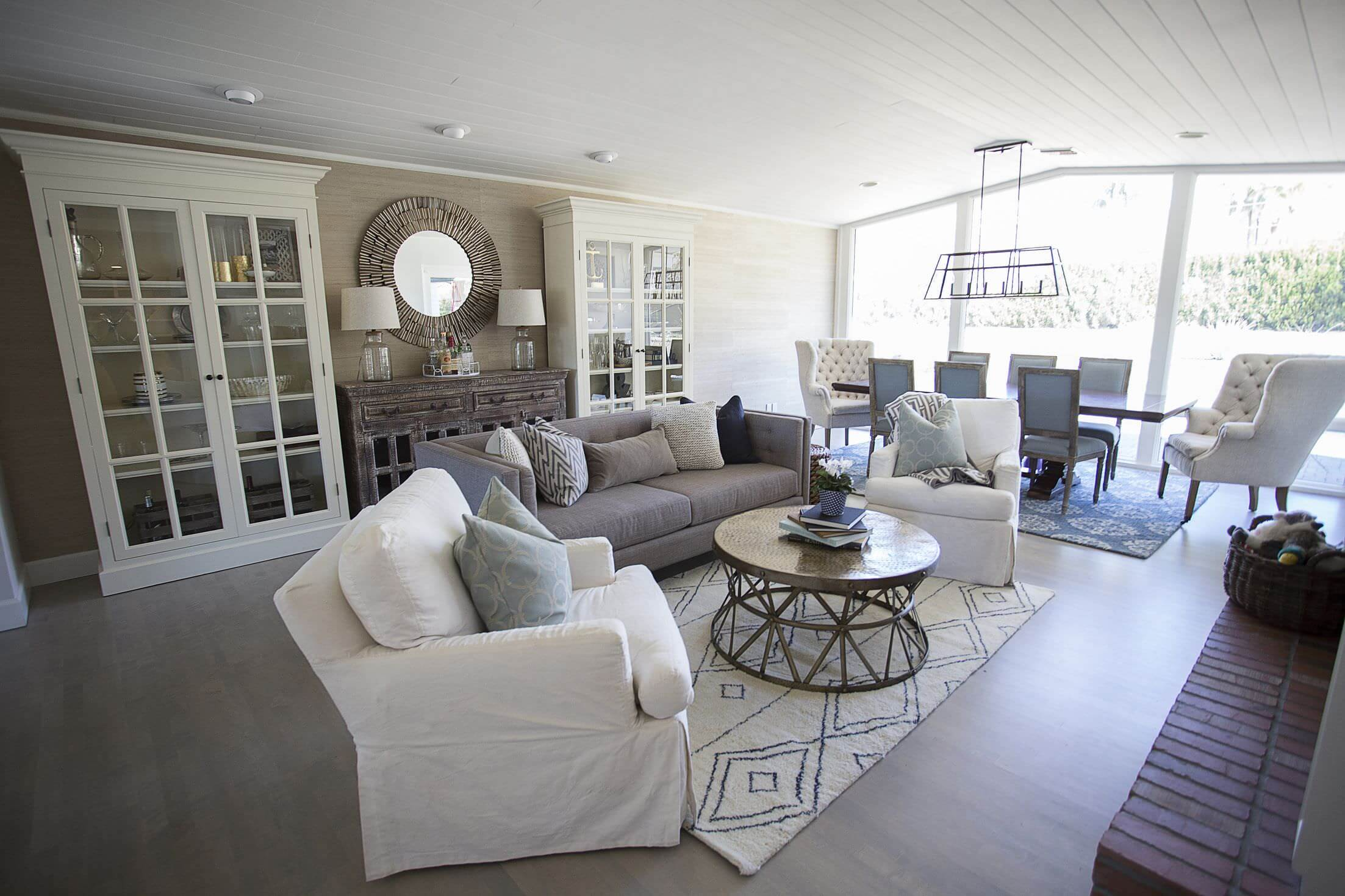 Large living space featuring a white cabinetry on the side and a set of comfy seats. There's a dining table set on the side as well.