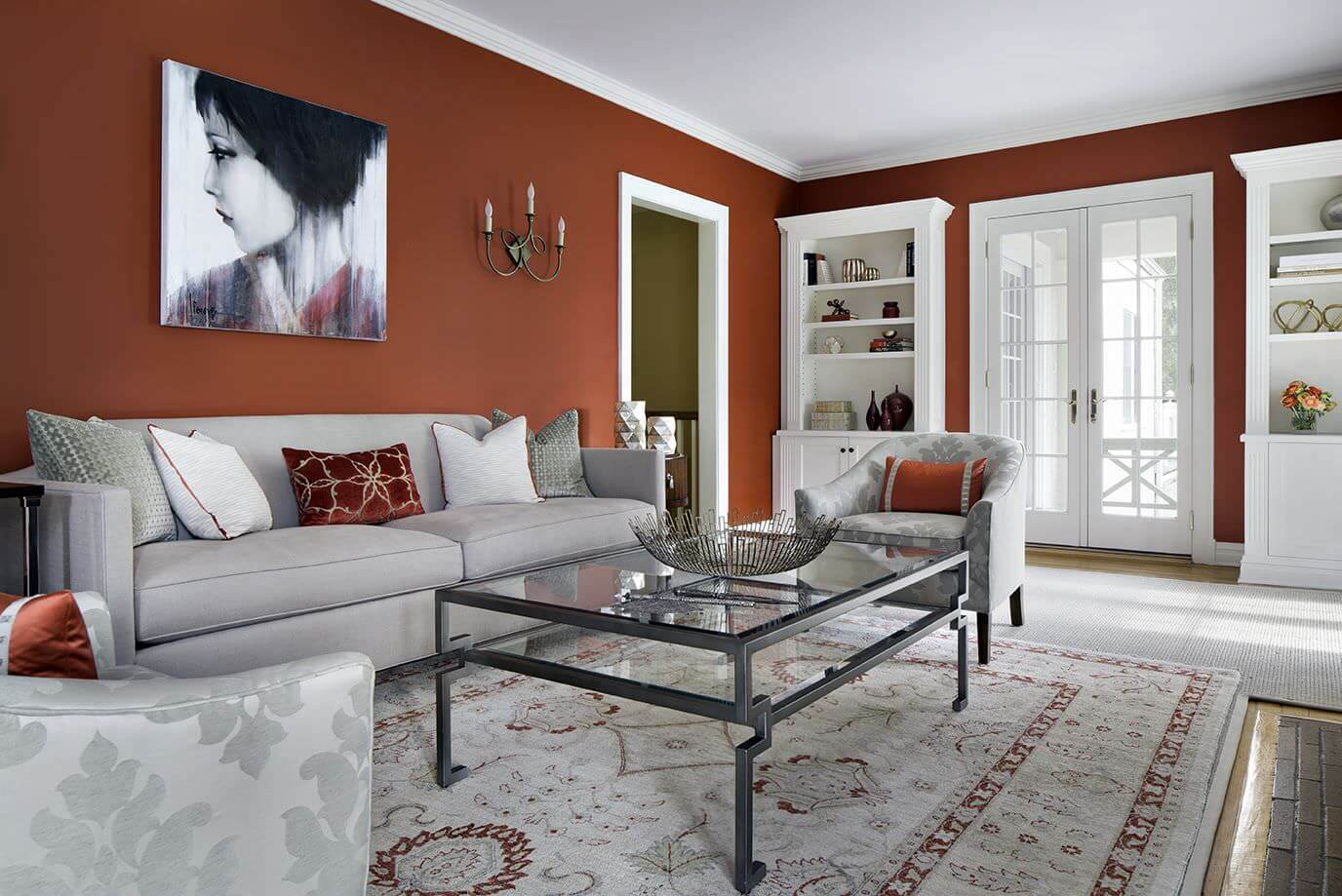 Spacious living space featuring rustic red walls along with white shelves and gray seats.