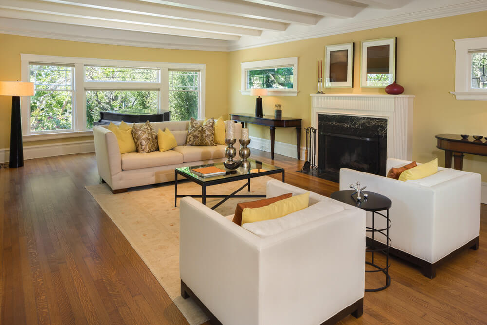 Large living room featuring hardwood flooring and cozy seats. It has a fireplace as well.