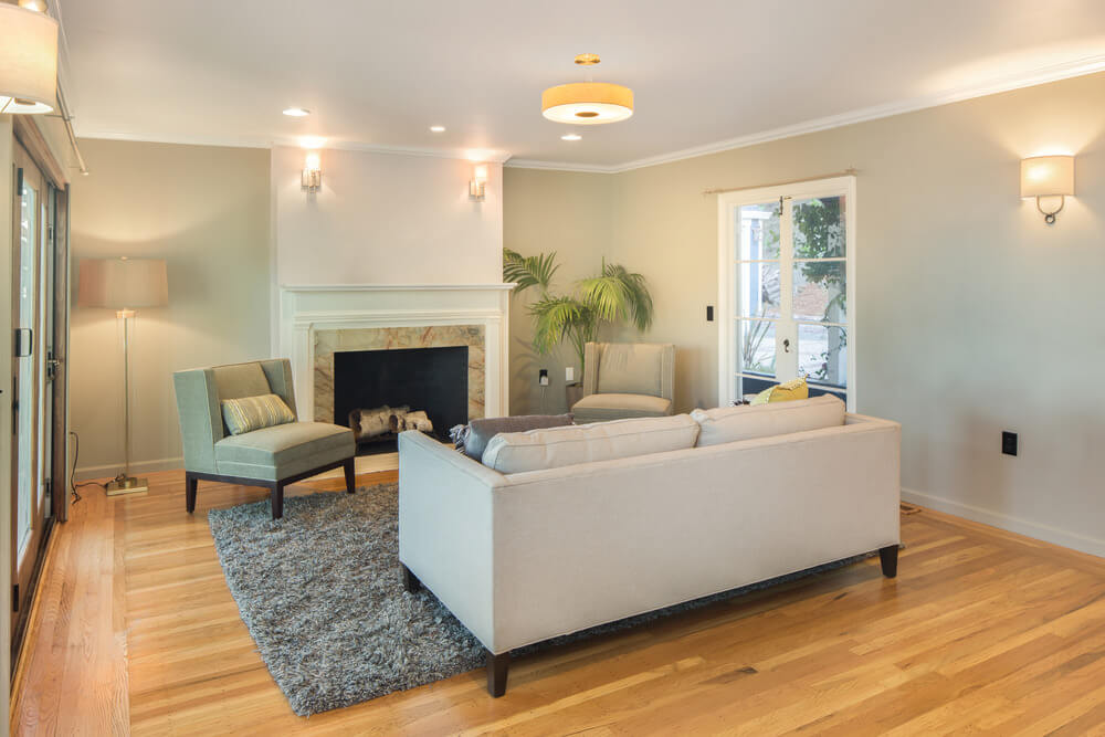 This living room features a couch, a gray area rug and a fireplace, along with wall lights.
