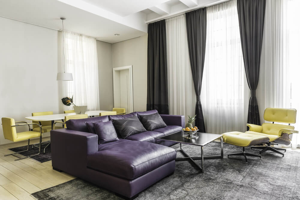 This living space features a purple L-shaped sofa along with a center table set on the gray rug covering the hardwood flooring.
