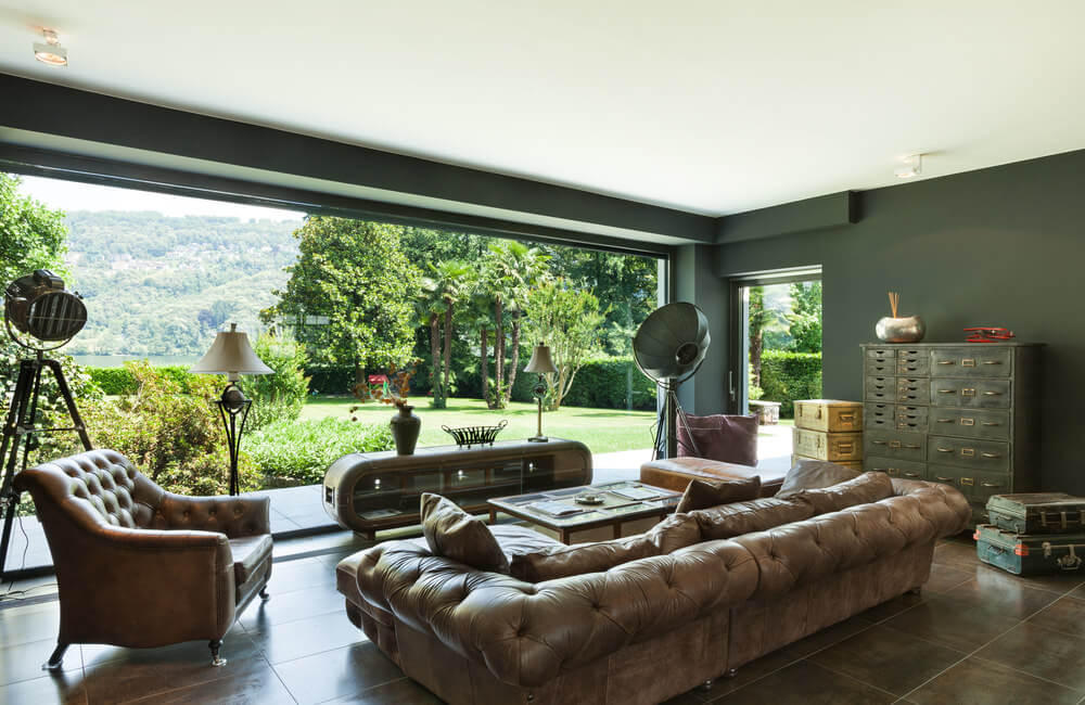 Large living room featuring brown leather seats that look so comfortable.
