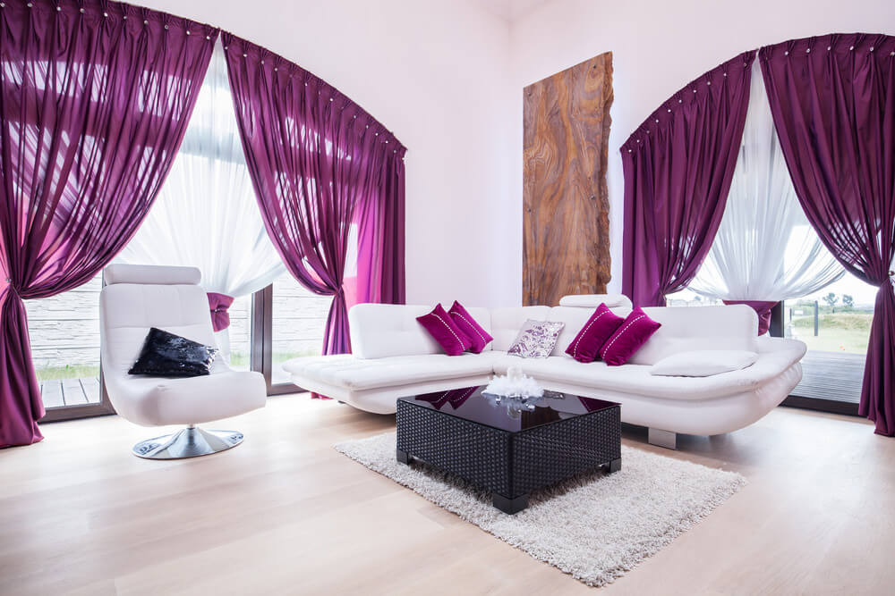 Spacious and bright living room featuring a white and purple color scheme. The white and purple window curtains look so stunning.