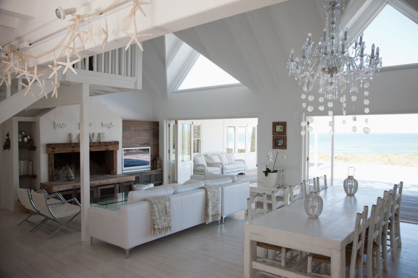 White living space featuring a white L-shaped sofa set in front of a wooden fireplace.