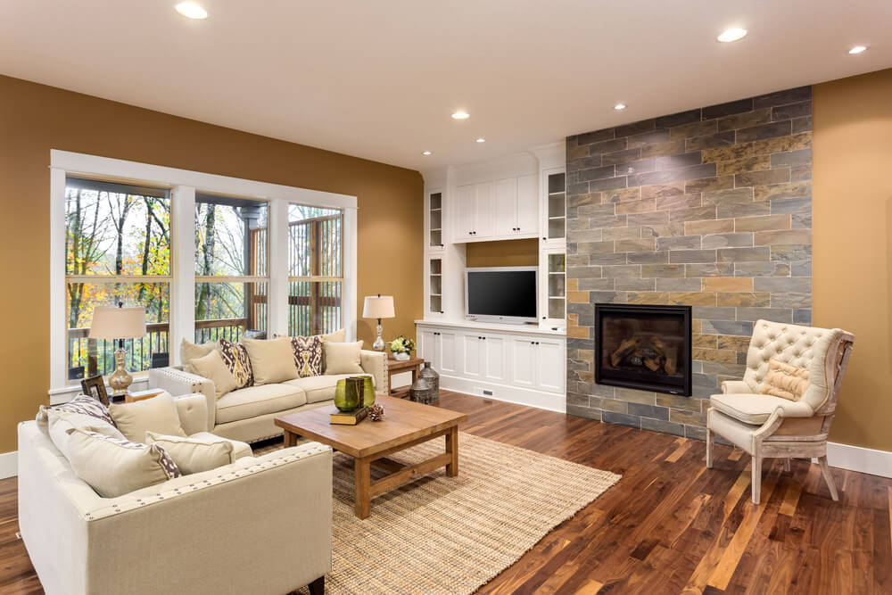 Spacious living room featuring hardwood flooring, classy seats and a fireplace, surrounded by brown walls.