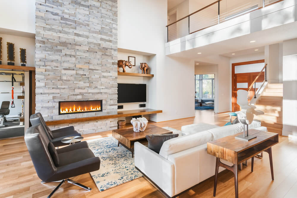 A bright and warm living space featuring modern seats, a rustic center table set on an area rug along with a fireplace.