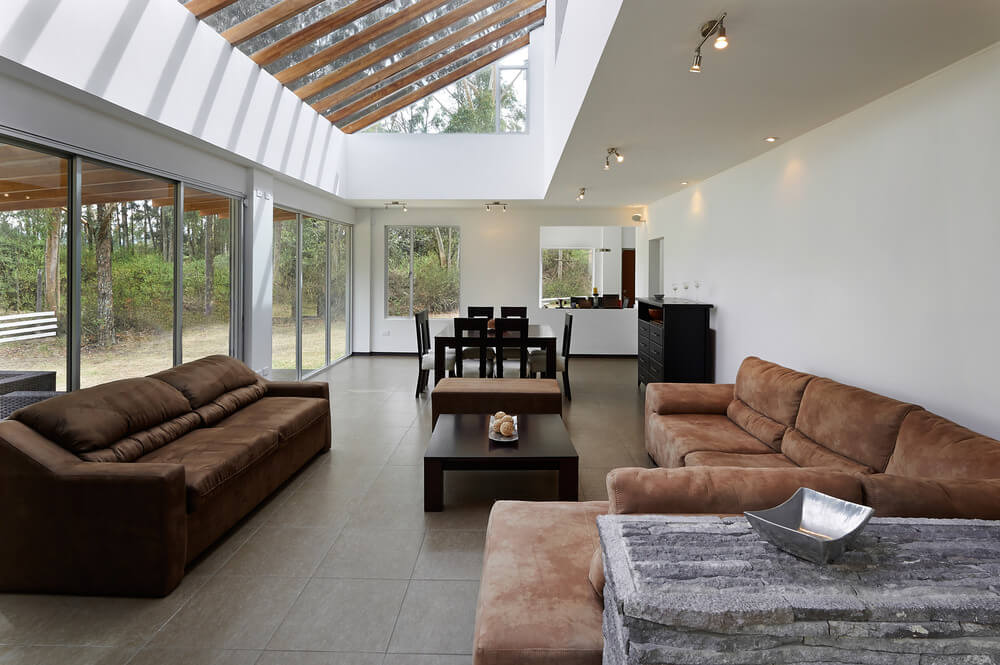 Large great room boasting elegant brown seats and a ceiling with skylight. The room is surrounded by white walls.