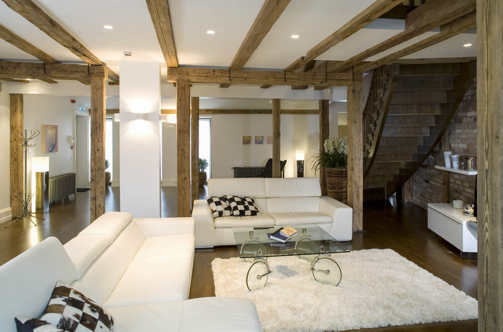This living room offers rustic pillars and hardwood floors, as well as a ceiling with exposed beams.
