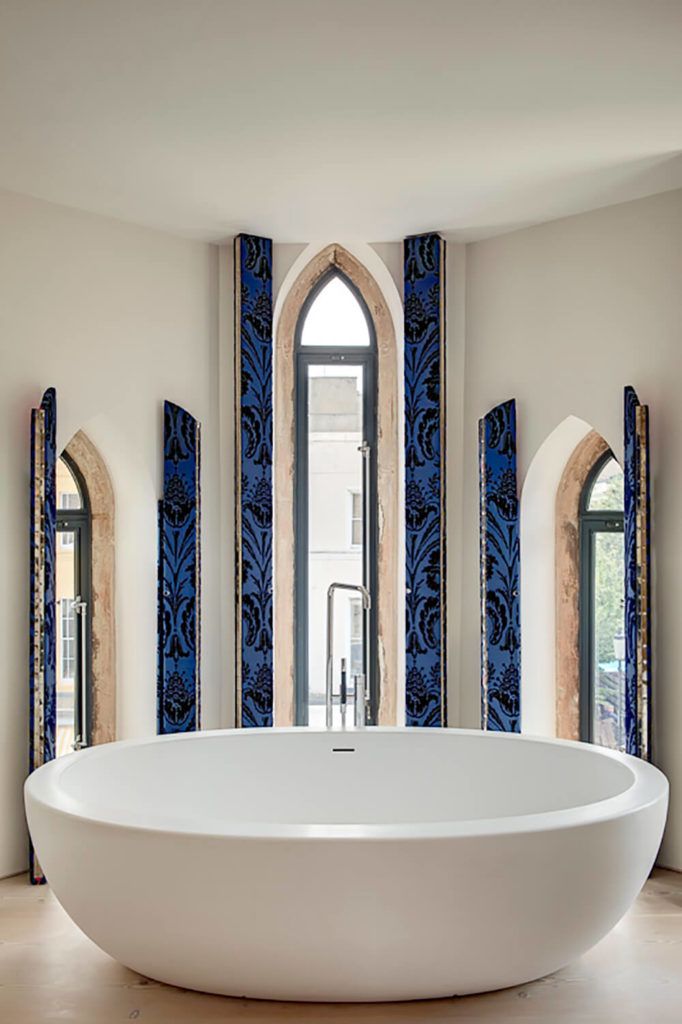 The primary bathroom features a trio of arched windows that let in plenty of light, but are narrow enough to still afford bathers plenty of privacy. Blue shutters allow for complete privacy.