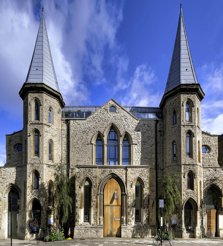 The exterior of this gorgeous building is that of a historic Gothic church in London. The building is symmetrical, with impressive stone features like the twin turrets and arched windows.
