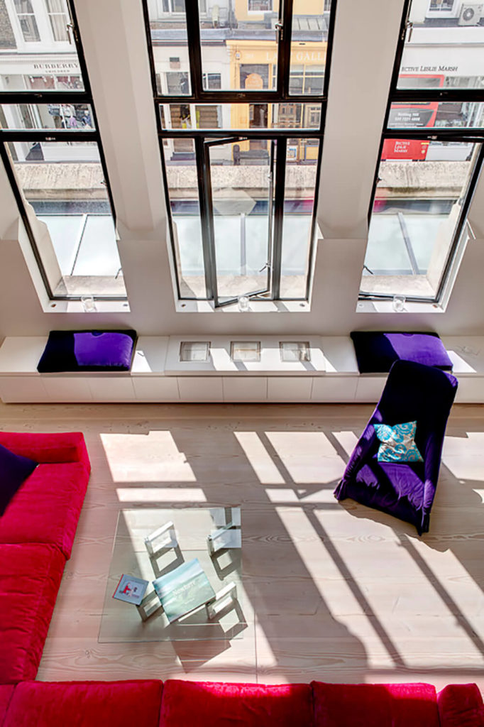 Here's another look at the living room area from above. The bright red sectional and purple accents are stunning against the light wood and white walls.