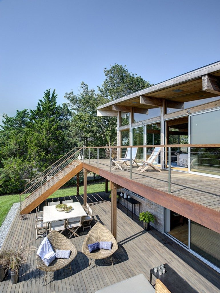 The sheer height of the upper level of this deck makes it feel more like a balcony, while simultaneously creating a covered deck area below. The wide stairs ensure guests won't bottleneck on the stairs.