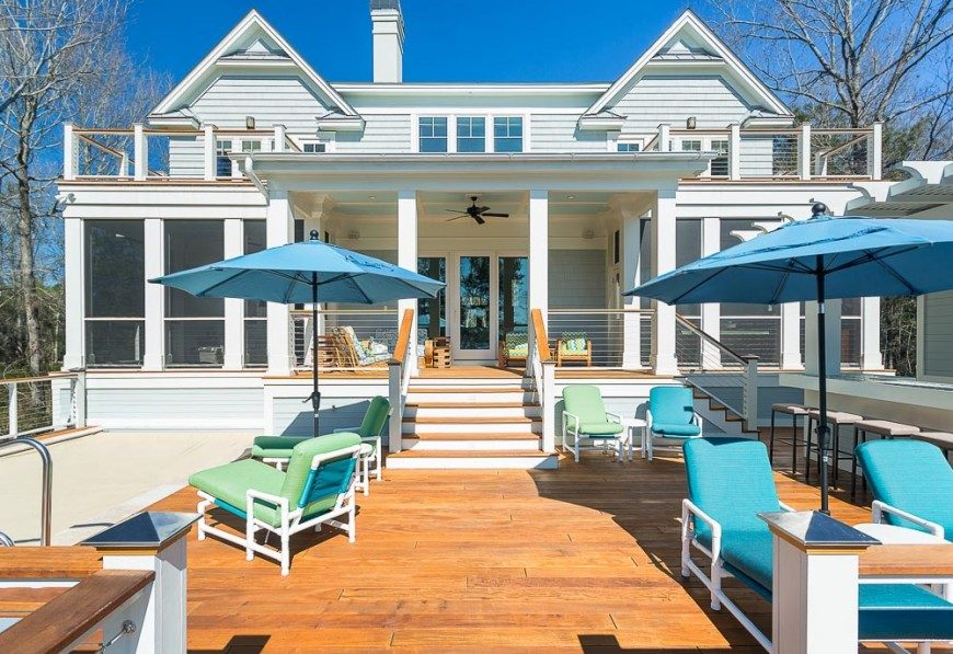 The deck of this lovely home is split into three distinct areas. The top level is a covered deck with lots of lounge room, while the lower areas are divided by a set of stairs. To the right is a bar area, while to the left is a hot tub and more sunbathing lounge chairs.