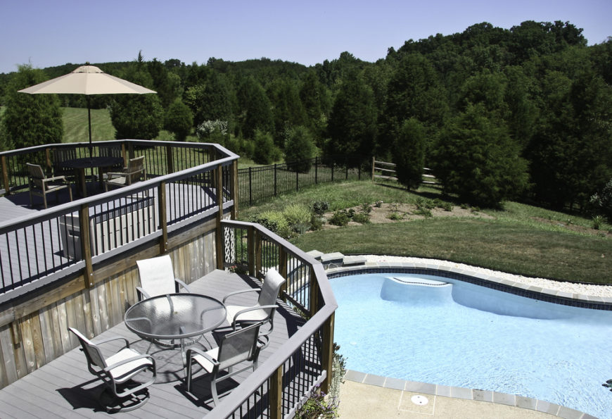This incredible set of decks are high enough to look out over the sizable swimming pool and the forested land beyond the backyard's fence. The top tier is a dining area, with a secondary table and chairs on the tier below.