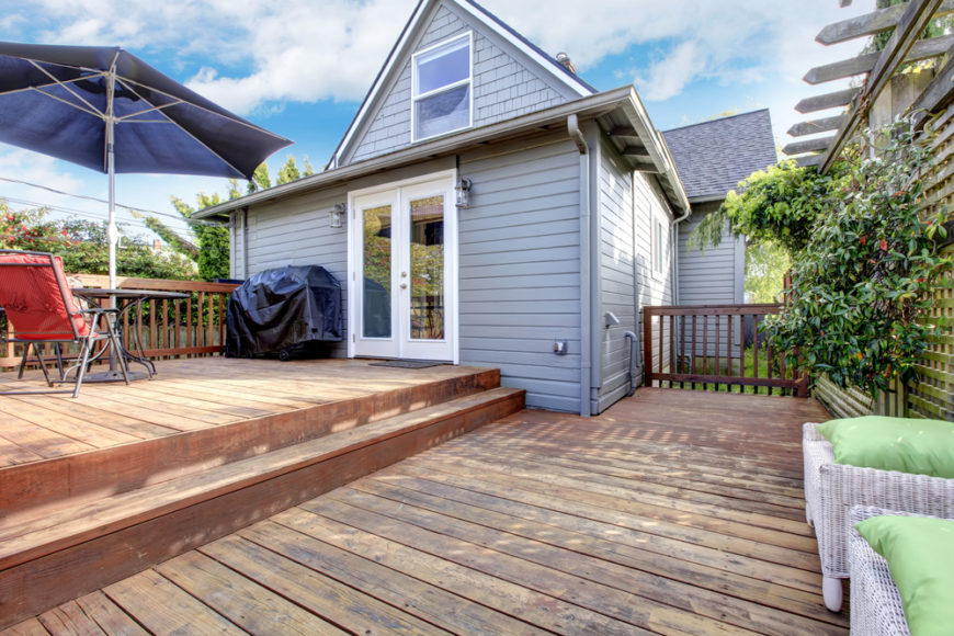 The home leads out onto the top tier of this spacious deck. The side of the lower level is screened in by vine-covered latticed screens.