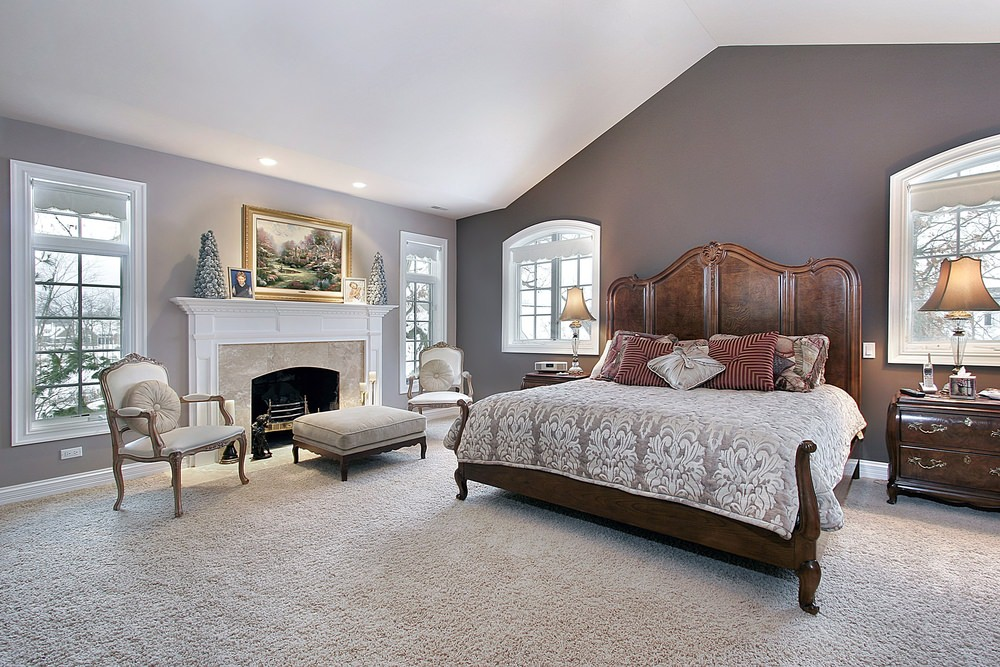 The personality of the room above is characterized with an interesting bed. The bed is massive, vintage and beautiful in combination with a modern fireplace and elegant sitting area.