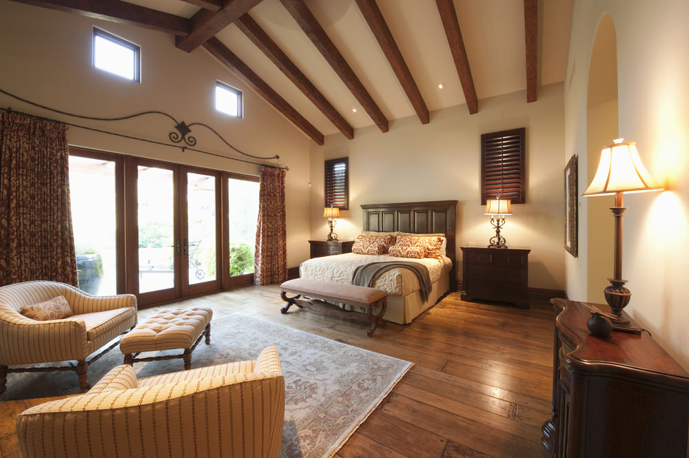 An ultra-large bedroom has plenty of room for a relaxing sitting area, with overstuffed chairs and ottoman.