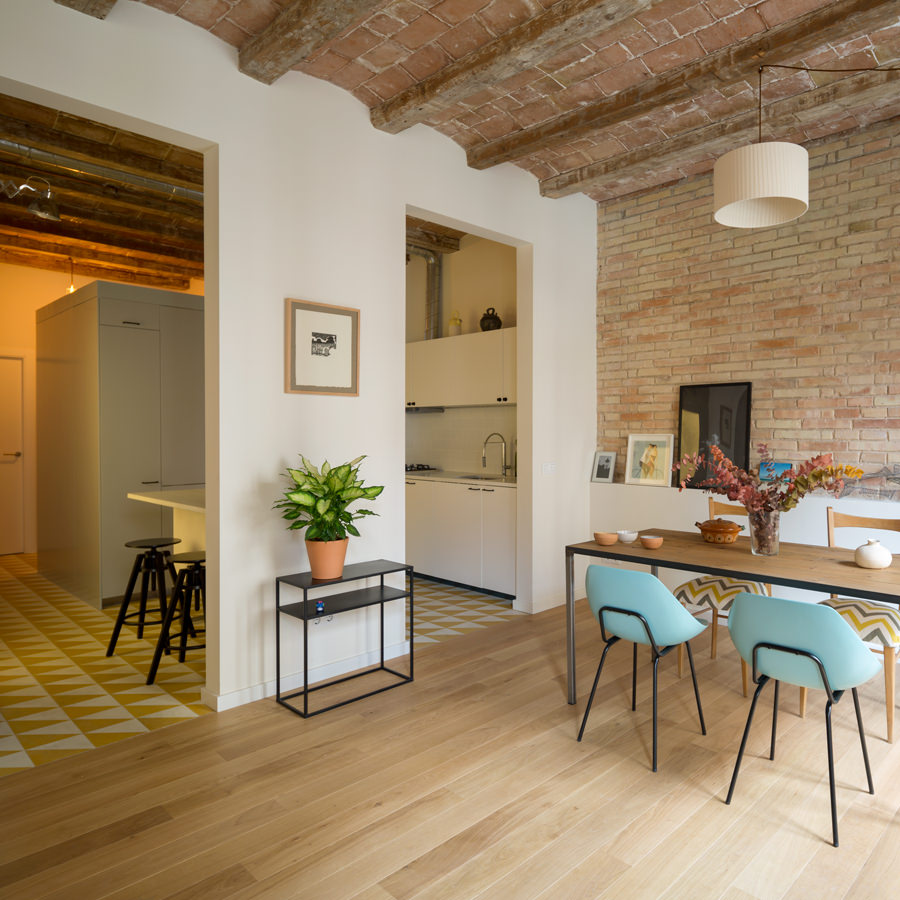 The dining area adjacent to the kitchen is quite accessible and stylistic with its cool wood palette and bright colored patterned floor design. The brick stone wall and ceiling preserve the interiors original construction.