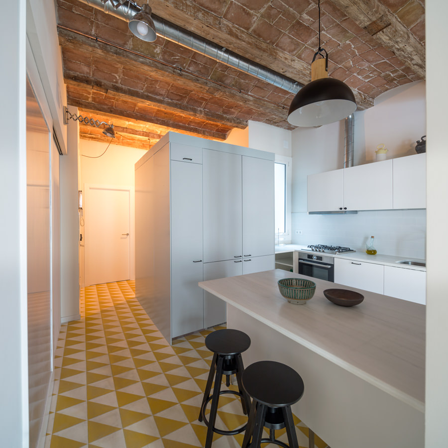 This is quite a space-wise idea as it has utilized the smaller space for passage way going to another door while the center part is assembled with a kitchen working table.