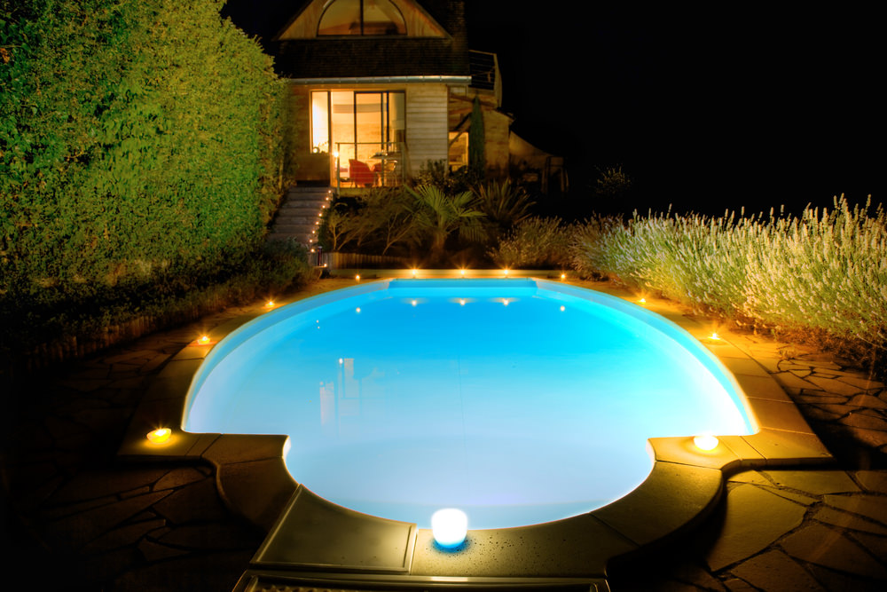 Outdoor inground pool lit up at night