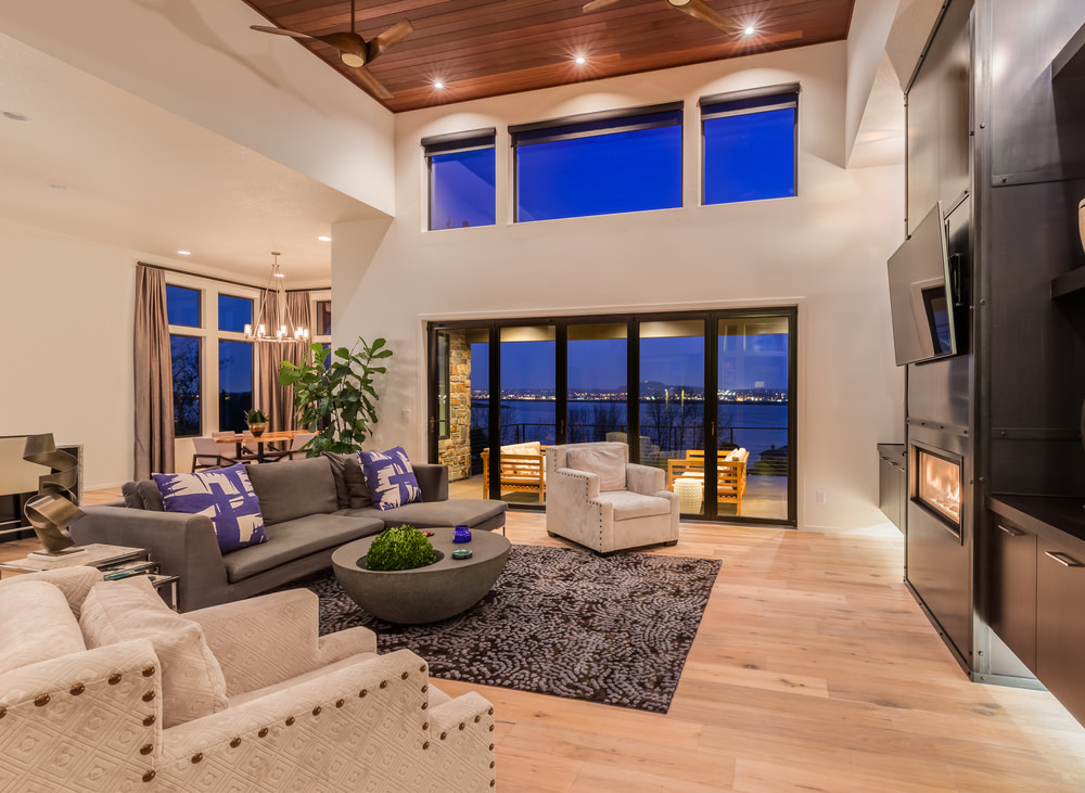 Wider window sizes and glass doors give way to fresh air and natural lighting. Also, the added dark shades of blue and black give life to this large living room. The space is quite wide and clutter free because of wall installed storage cabinets. As you can notice, there are a few touches of greenery inside, one of them is planted in a sleek center table.