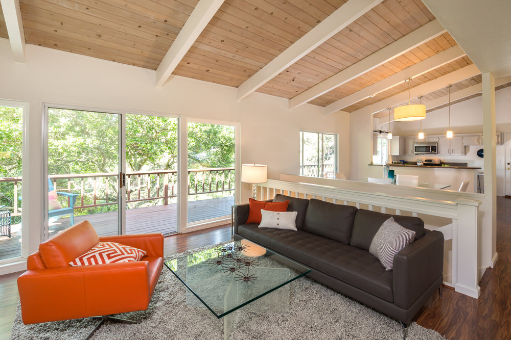 Revealing timbers on the ceiling and the walnut floor with a few striking orange shades of pillows and a seat highlight the monotone colors of the design.