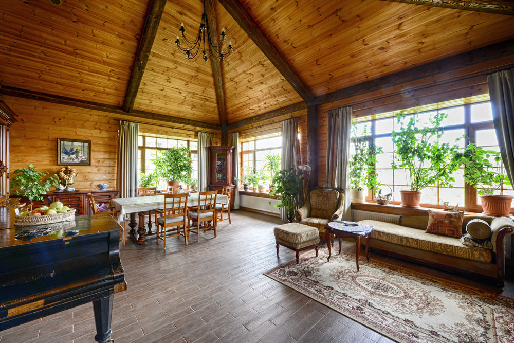 Cathedral ceiling on high top while the rustic and old fashioned furniture and carpeting on the floor completes the authentic cabin design.