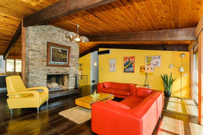 The bright orange leather sofa set in this living room is quite stunning and bright alongside the yellow armchair, center table and wall.