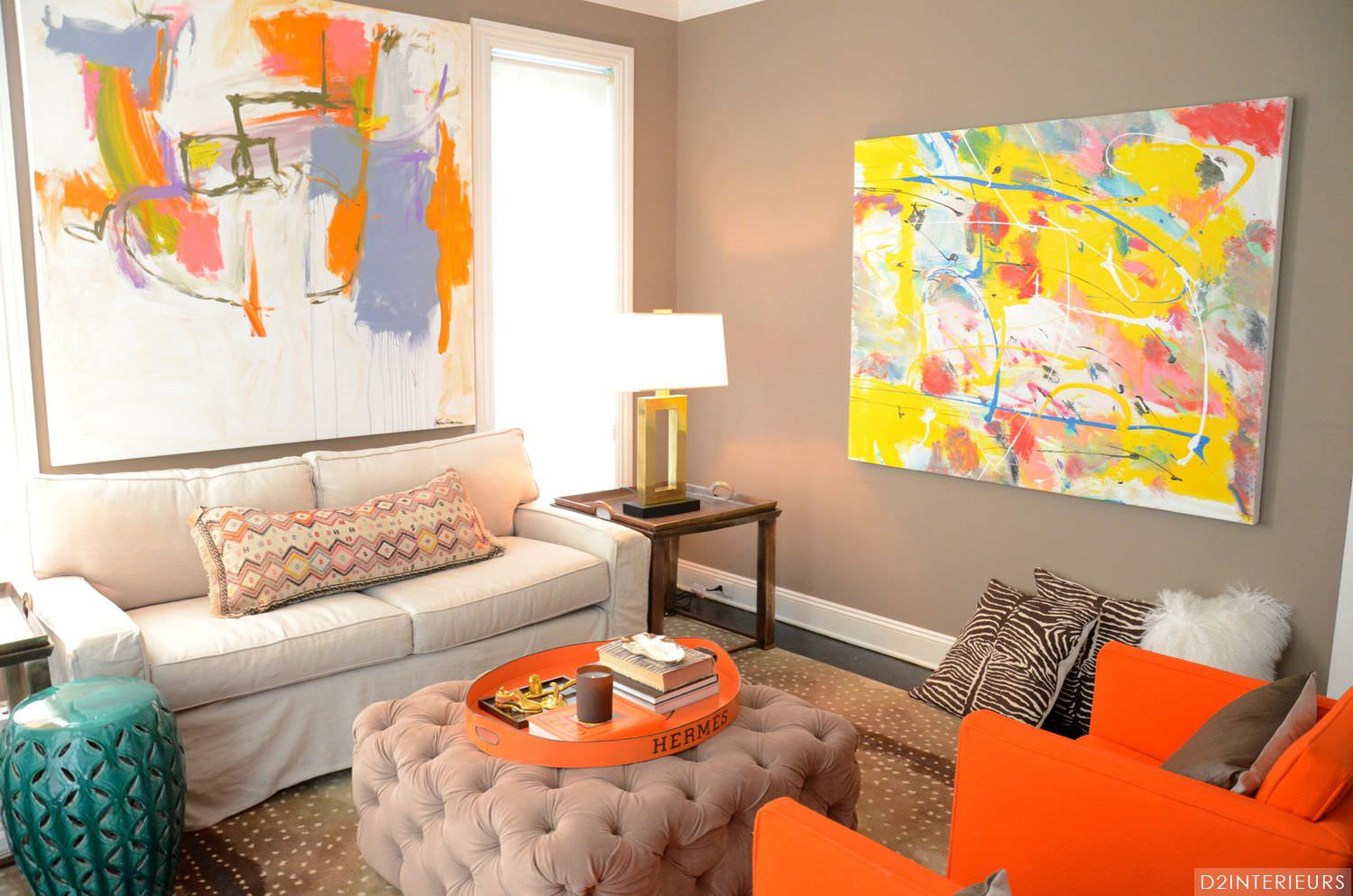 Name all the orange things in this image. Well, let's start it with the pair of orange armchairs, the orange tray on top of the ottoman, the orange patterns on the bolster pillow, and some orange accents on the artwork hanging on the wall. These bright colored items seem to highlight what could otherwise be a gloomy living room and give it a cheerful atmosphere.