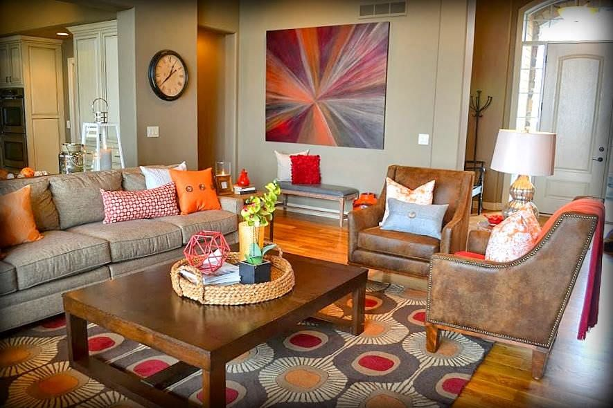 A variety of orange touches and shades are found in here. Artsy orange shades in the painting, light orange on the floor rug, orange cloth on the leather seat, and some orange throw pillows all go together in this slightly rustic and old fashioned living room. They obviously light up the room.