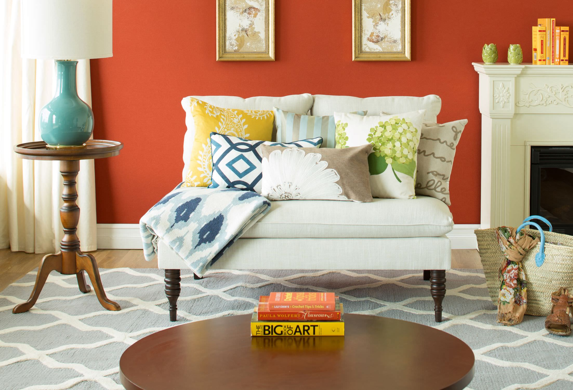 The simple orange background wall, a few books stacked as a centerpiece, and the fireplace panel decor are enough to brighten up this living room's otherwise monotonous color scheme.