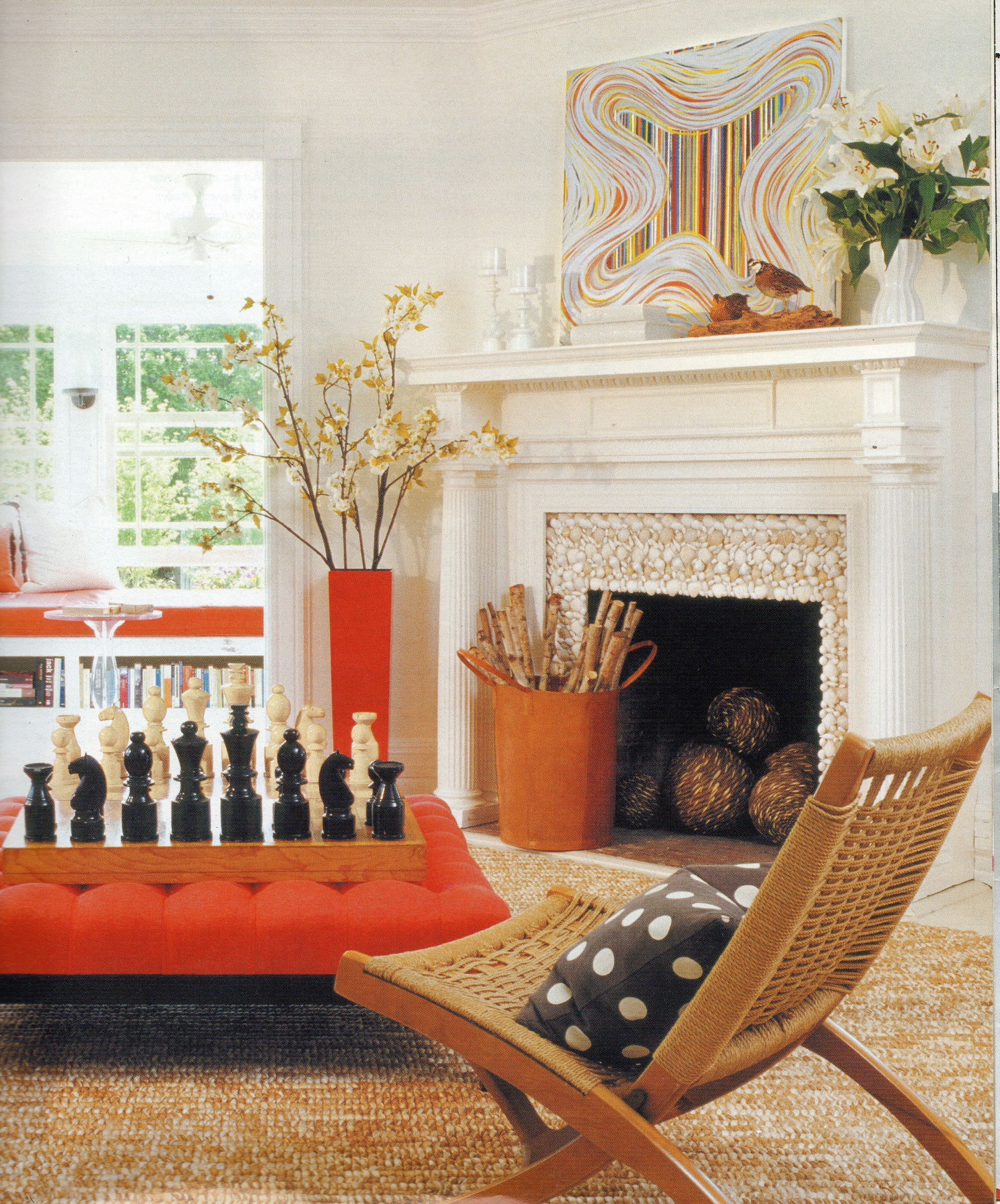 The delicate color selection of this living room departs from common living room color schemes by incorporating orange. The center ottoman mounted with a chess board and oversized pieces, the vase, window bench, firewood holder and the artwork are all eye catching.