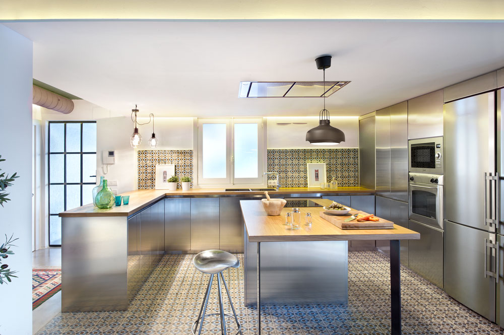 The geometrical Asian tile patterns on the flooring and wall are quite stunning while the steel cabinets and kitchen fixtures shimmer as the light shines on them.