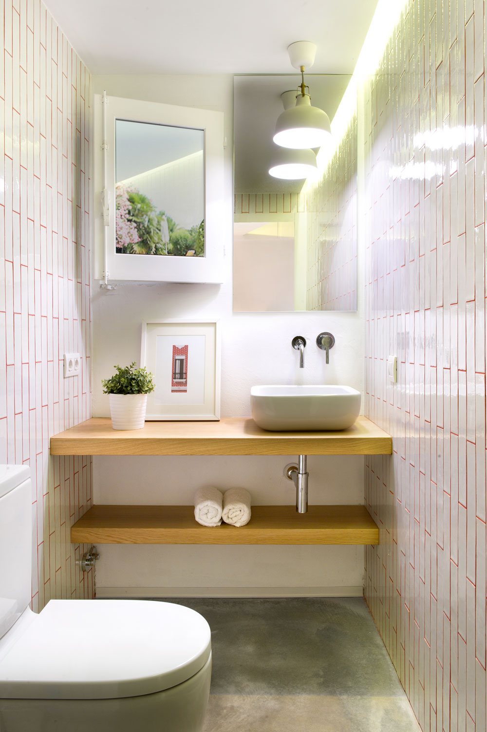A tranquil and relaxing rest room with pure white touches on the walls, while the floor seems industrial as it remains in its raw and concrete look without tiling. There are a few touches of nature on the frame, potted plants and wooden shelves.