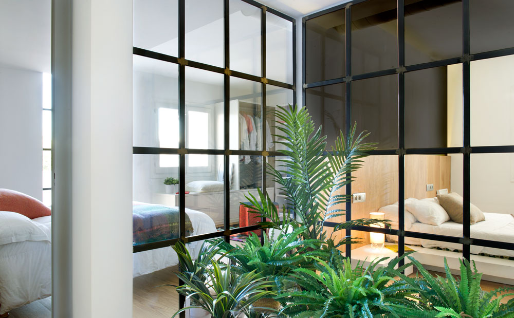 Glass wall bedrooms see through to the planted greenery outside them.