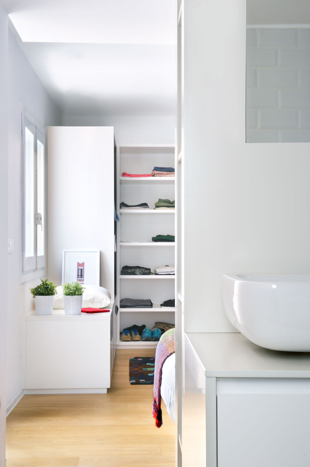 Simple and plain lines and colors on the cabinets show the minimalist side of this design. The open closet exposing the contents gives it a little twist.