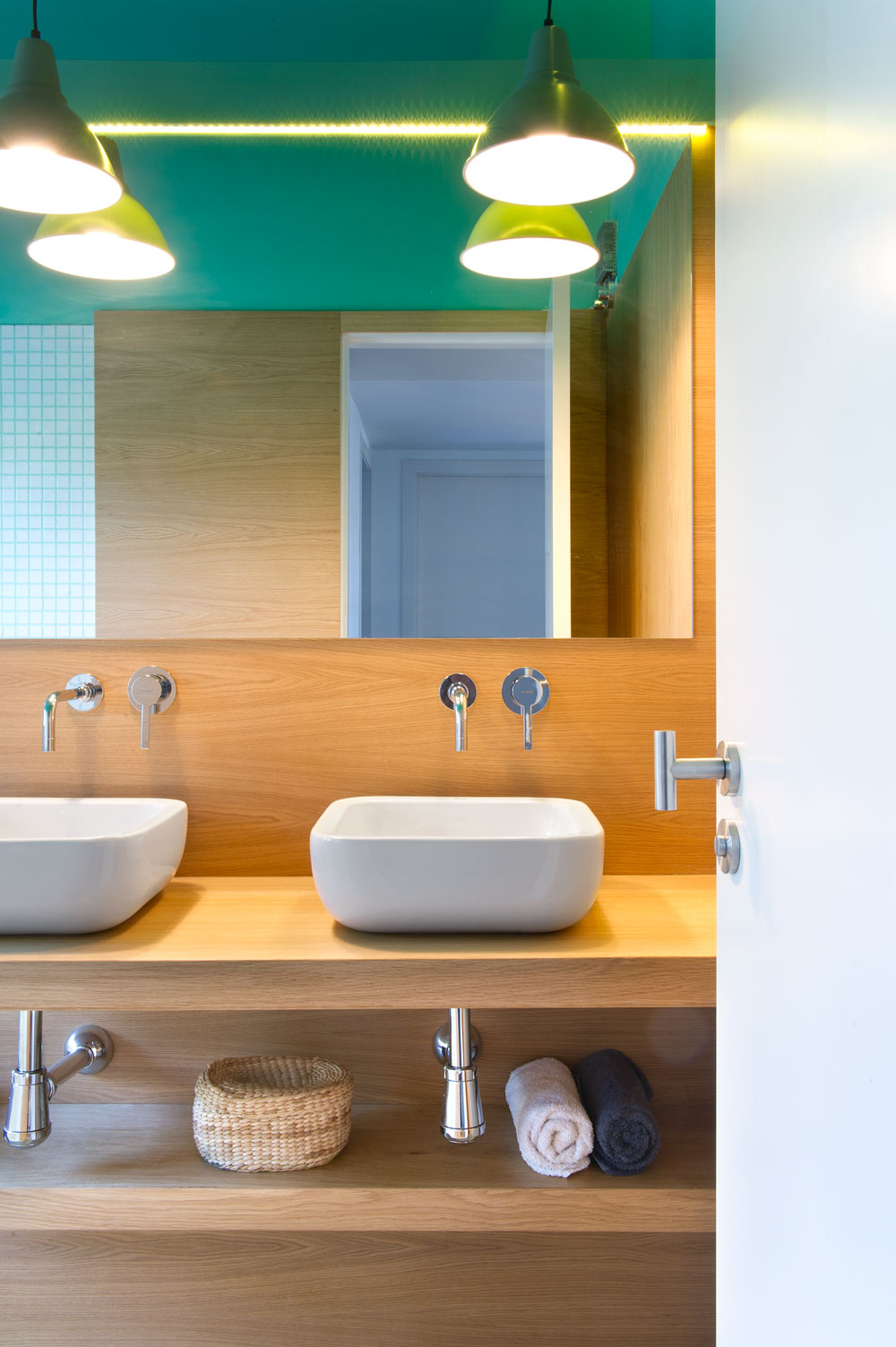 A pair of sinks symmetrically installed on a wooden counter top with a shelf underneath for towels and other toiletries.